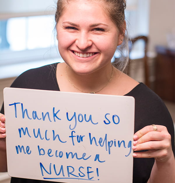 "College of Nursing BSN student Victoria Sanna poses holding a sign that reads ""Thank you so much for helping me become a nurse."""