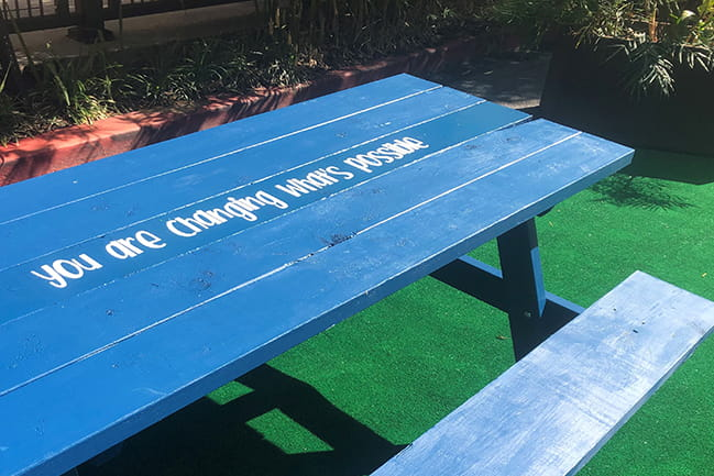 Picnic table with motivational message: 'you are changing what's possible'